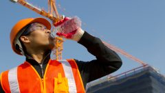 worker man  as he drinks from a plastic water bottle on construction site